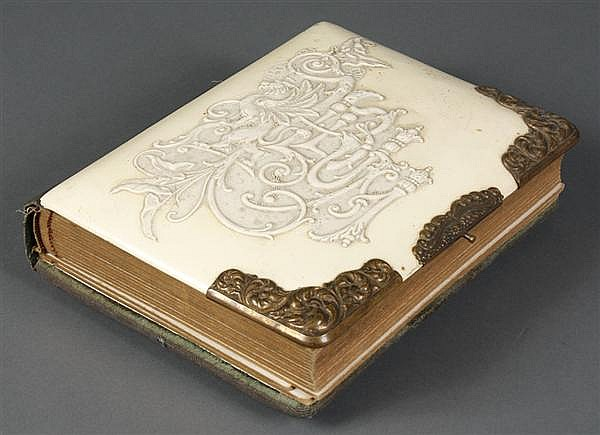 CELLULOID PHOTO ALBUM - Embossed ivory colored celluloid photo album depicting griffins and botanical motifs. The album is filled wi...