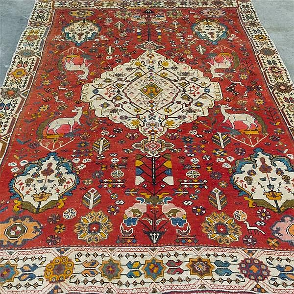 CARPET: HAND-KNOTTED PERSIAN SHIRAZ - Wool on a cotton warp with red field, large rhomboid central medallion surrounded by multiple....