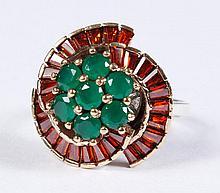 EMERALD & GARNET RING - A cluster of 7 round prong set round green emeralds is encircled with three swirls of orange-red garnet bagu...