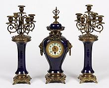 THREE PIECE CLOCK GARNITURE SET - Comprising a centerpiece clock in urn form with porcelain face and pair of five-branch candelabra....