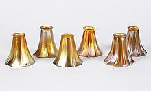 SIX STEUBEN AURENE ART GLASS SHADES - Ribbed trumpet form in gold iridescent hues. Apparently unmarked. 5.25