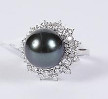 CULTURED BLACK PEARL & DIAMOND RING - The central Tahitian cultured round black pearl is set within a stylized diamond floret bezel...