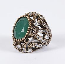 EMERALD, WHITE TOPAZ AND ROSE GOLD RING - The dome ring features a central oval emerald set within a bezel of gold prongs above an e...