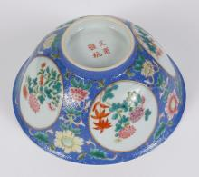 CHINESE PORCELAIN SGRAFFITO BOWL - Having a blue sgraffito ground set with reserves of flowers. A modified dharma wheel is on the bo...