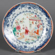 FAMILLE ROSE CHINESE PORCELAIN PLATE - With scene of a man showing a flower to women inside a garden pavilion. Stylized blue foliate...