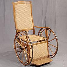 WHEEL CHAIR - Antique American oak with three-wheel configuration, adjustable tall back, caned inserts, iron fittings and steam-ben...