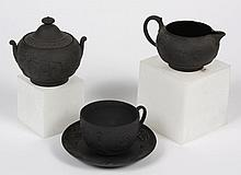 FOUR ANTIQUE WEDGWOOD BLACK BASALT ITEMS - Comprising a sugar bowl with lid and a creamer both with Greek/Roman neoclassical scenes....