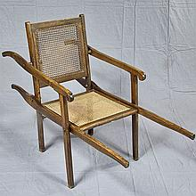 TRANSPORT CHAIR - Antique of mixed woods in folding configuration with caned back and seat, integral handles; fore and aft. Conditio...