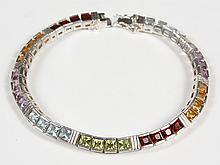 STERLING SILVER BRACELET WITH MULTI-COLORED GEMS - The bracelet is a flexible ribbon of 36 faceted gemstones set in square sterling...