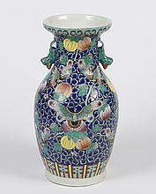 CHINESE PORCELAIN VASE WITH BUTTERFLIES AND GOURDS - Rouleau form with flared mouth and faux handles modeled in the shape of a squir...