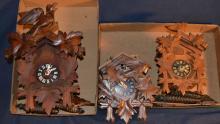 Three wood carved cuckoo clocks, as is