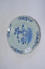 Assiette en porcelaine, au pourtour polylobé, à décor de pin et floral. Bleu blanc sous couverte glacée. Accidents et       collage. Ø.23cm.