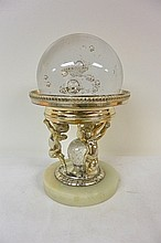 A crystal ball supported by a base of 3 cherubs