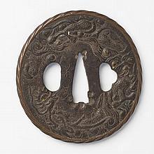 JAPON - Époque EDO (1603 - 1868) Nagamaru gata en fer à décor ciselé en hira bori d'un dragon pourchassant la perle sacrée parmi les..