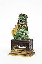 Petite chimère en porcelaine émaillée vert et jaune assise sur son socle de forme rectangulaire, avec son petit
