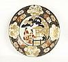 Grande coupe en porcelaine décorée en bleu sous couverte, rouge de fer et émail or de deux jeunes femmes près d'une maison, l'aile o...