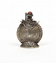 Flacon tabatière en métal de forme arrondie sur pied douche, orné sur une face d'un lion des neiges dans un médaillon, d'un vase fle...