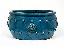 Vasque en grès émaillé turquoise, la panse ornée en relief de quatre masques de chimères et de clous