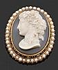 Broche ovale en or jaune, ornée d'un camée agate représentant un profil de femme, dans un entourage d'émail noir et de demi-perles. X