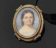 Broche de forme ovale en or jaune, ornée au centre d'une miniature polychrome, représentant une jeune fille en buste. Signée à gauch..