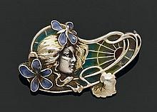 Broche en argent figurant un visage, dans un décor de fleurs partiellement émaillé en plique à jour. (petits accidents à l'émail). E..