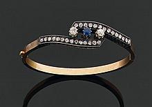 Bracelet rigide ouvrant en or et argent à entrelacs orné d'un saphir entre deux diamants de taille ancienne et deux lignes de diaman..