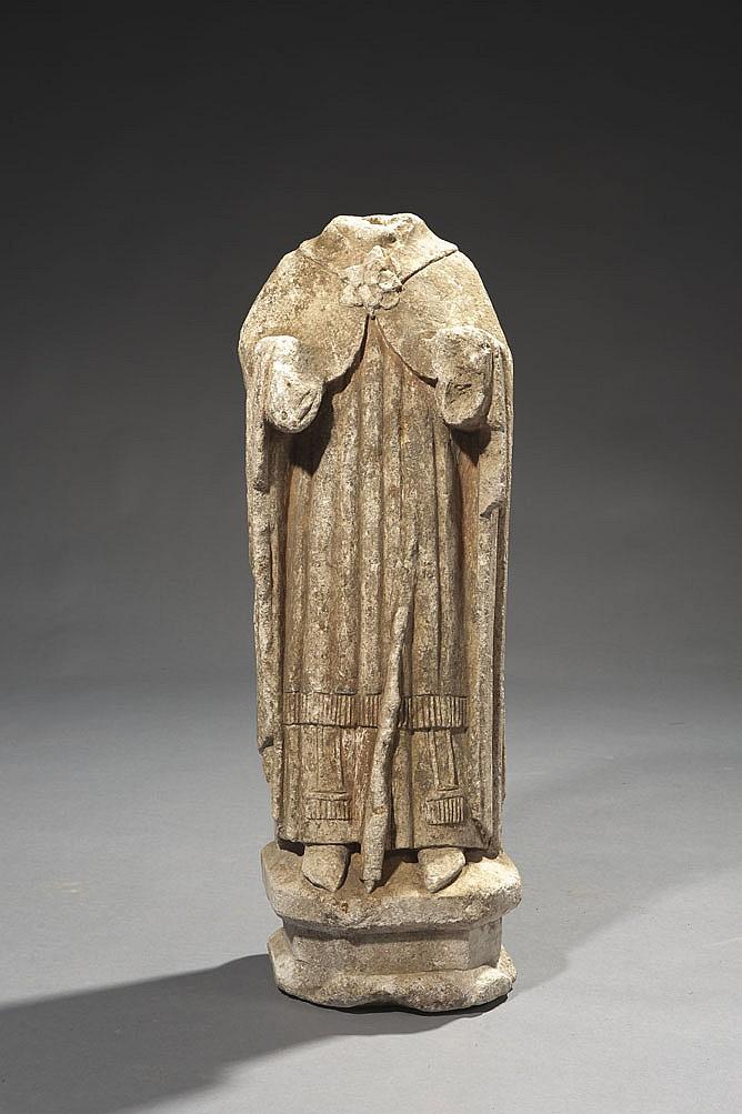 Statue acéphale d'un saint évêque en pierre calcaire sculptée en ronde-bosse avec restes de polychromie. Debout, il porte une tunique