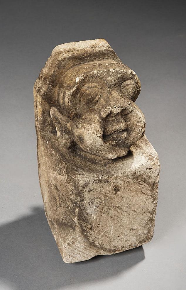 Modillon en pierre calcaire sculptée d'une tête aux traits grotesques avec globes oculaires proéminents, nez épaté, joues épaisses e..