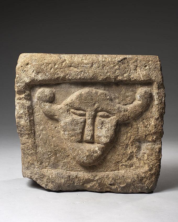 Pierre calcaire de forme rectangulaire sculptée d'un panneau en réserve avec bas-relief représentant une tête mi-taureau mi-humaine