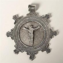 Médaillon en argent. Face avec Christ en croix, au revers, Vierge au manteau ; encadrement àdouble spirales supportant sept fleurons...