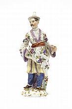 Meissen Statuette représentant un Chinois debout vêtu d'une tunique à décor polychrome de fleurs des Indes et tenant un écran dans l...