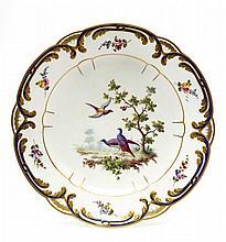 Sèvres (genre de) Assiette à palmes à décor polychrome au centre de trois oiseaux sur une terrasse l'aile décorée de bouquets de fle...