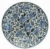 Japon Plat rond en porcelaine blanche à décor en bleu sous couverte de branches fleuries et feuillagées. XVIIIe siècle  Diamèt...