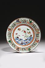 CHINE Époque KANGXI (1662-1722) Assiette en porcelaine décorée en bleu sous couverte et émaux polychromes de la famille verte d'un c..