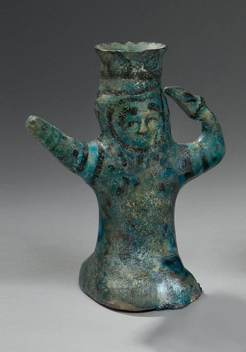 Figurine féminine assise, un bras tendu, l'autre recourbé