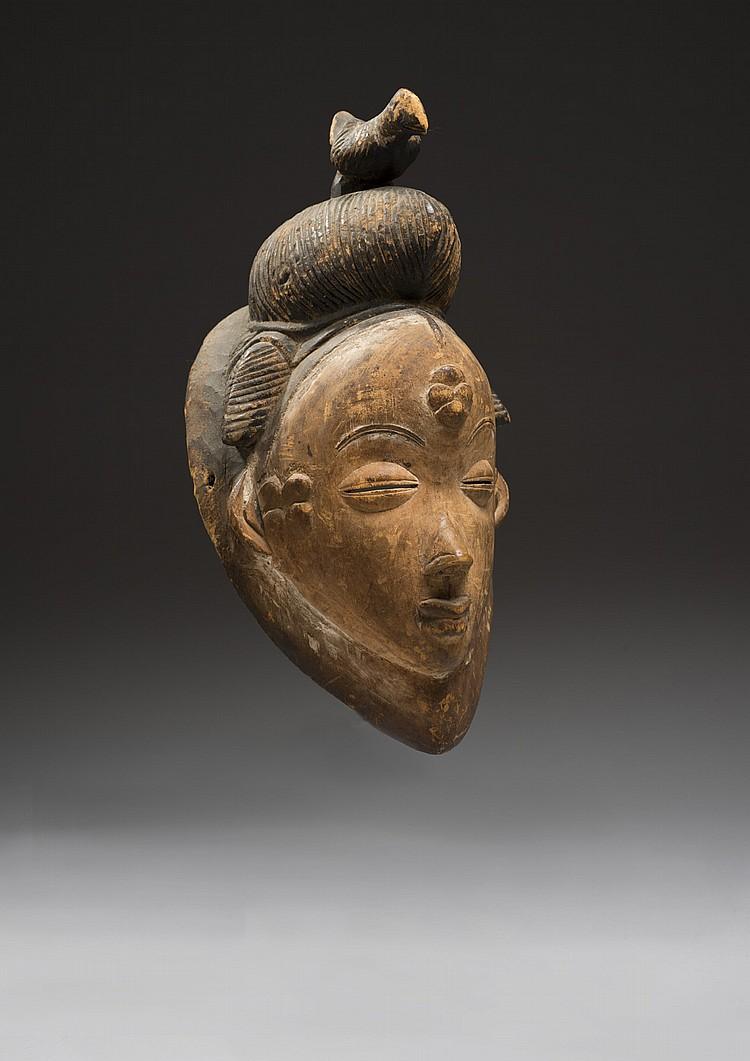 Punu, Gabon Rare et ancien masque scarifié dont la coiffe à coque est surmonté d'un oiseau