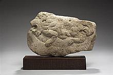 Bas-relief en pierre calcaire sculptée représentant un lion allongé rugissant, la gueule ouverte