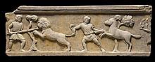 Partie de frise en marbre sculpté en bas-relief de jeunes hommes, l'un combattant un lion, l'autre dressant un cheval