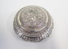 An Indian White Metal Circular Box decorated with figures and foliate scrol