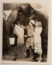 Clyde and Harriet Beatty Inscribed and Signed Photograph. 1947. Depicts Clyde Beatty in safari gear with wife Harriet and a circus elephant. Bold inscription reads, 'To our friend Pat. Best wishes Harriett & Clyde.