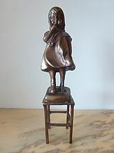 Lovely bronze sculpture of a girl on chair.
