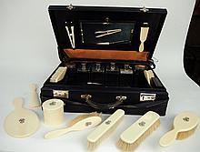 Dans une valise en cuir bleue marine, nécessaire de toilette comprenant un nécessaire en ivoire et cristal. Avec sa housse.