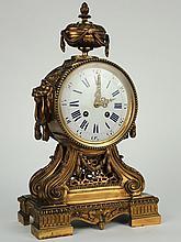 Pendule de style Louis XVI en bronze patiné à décor de muffles de lions et d'un vase à l'antique. Mécanisme signé Richond Frères à Paris. H. : 43 cm