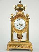 Pendule-cage de style Louis XVI en bronze doré à décor de rinceaux feuillagés, de draperies, de noeuds de ruban, surmonté d'un vase à l'antique. H. 44 cm