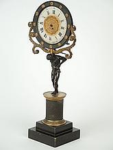 Pendule dite veilleuse en bronze ciselé, patiné et doré représentant la figure d'Atlas portant le monde sur ses épaules.
