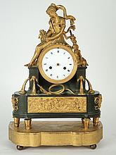 Pendule borne Directoire en bronze et bronze doré et ciselé à décor d'une allégorie de l'automne assise sur le cadran, d'un serpent repoussé par un flambeau au-dessous, la base ornée d'un bas-relief représentant une scène mythologique.