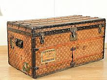 VUITTON.  Importante malle en cuir et bois, intérieur en soie ivoire capitonné, comprenant ses deux plateaux à compartiments.