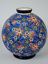 LONGWY.  Vase boule à décor de branchages fleuris en émaux polychromes.