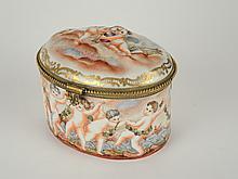 Boite ovale en Capodimonte à décor de puttii (petit défaut de cuisson à l'intérieur). H. 11,5 cm