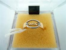 A GOLD BAND RING, open pierced central oval plaque, two white side stones. Size L. Weight 1.7g.